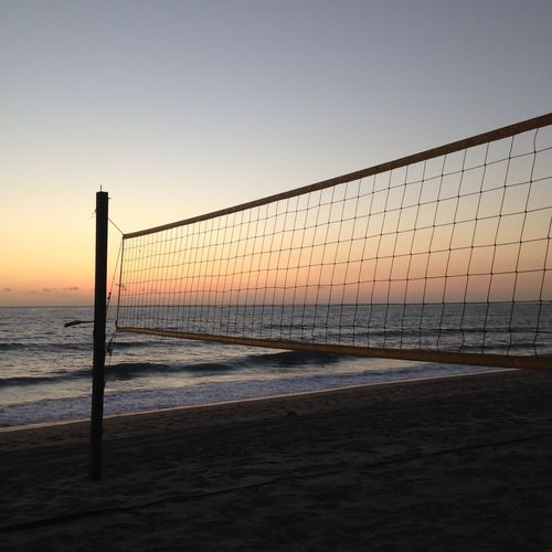 Volleyball net on beach against sea during sunset