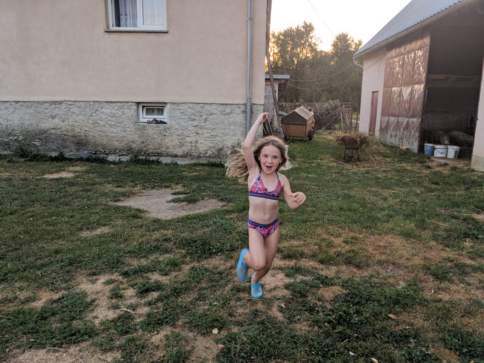 Full length of a girl standing in front of house