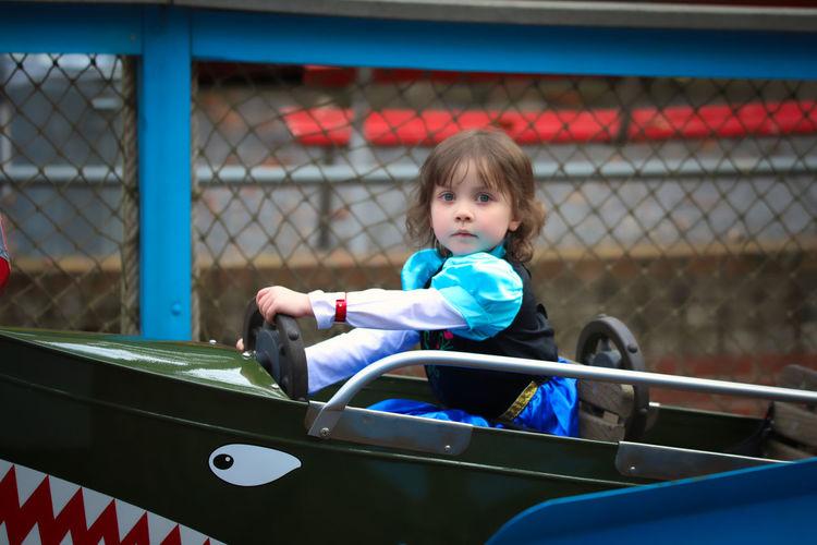 Portrait of cute girl sitting in bumper car at amusement park