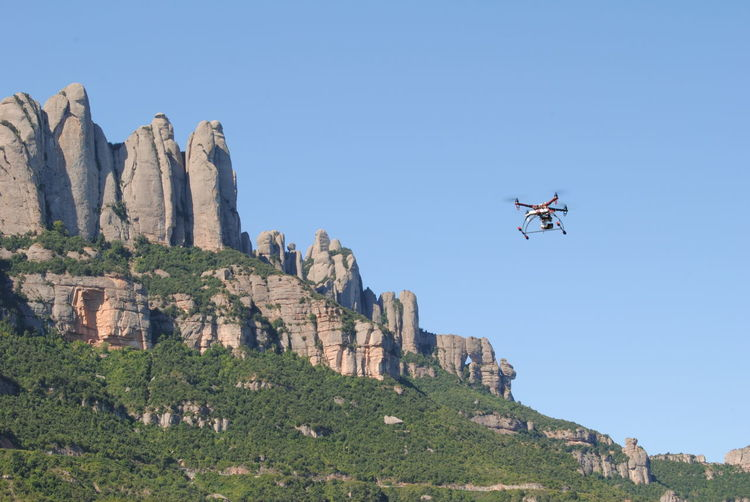 Low angle view of octocopter flying by rocks against clear sky