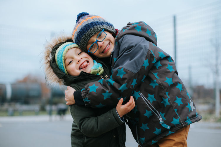 Cute boys embracing while standing outdoors during winter
