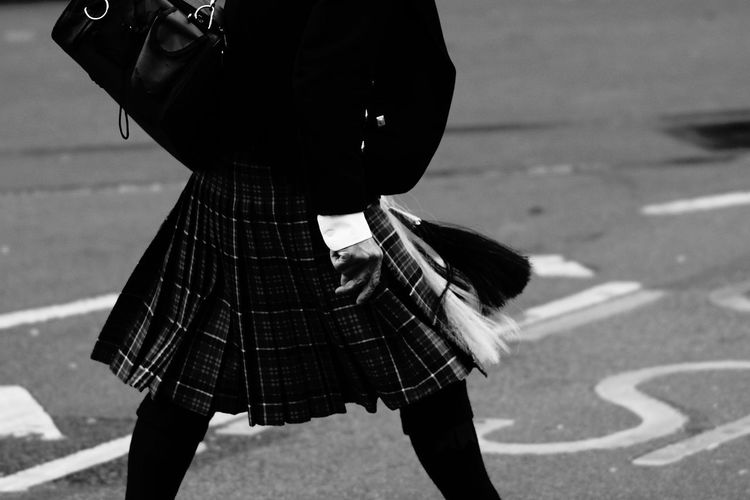 Midsection of person wearing kilt while walking on road