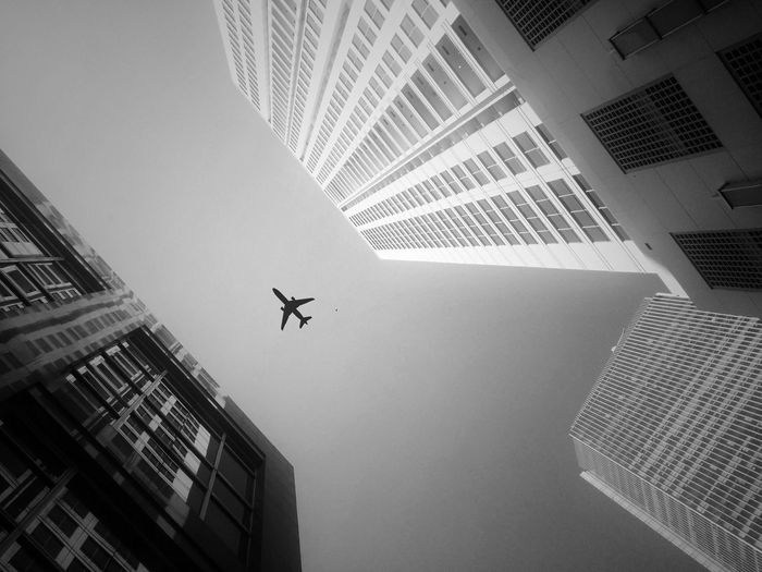 Directly below shot of airplane flying amidst buildings