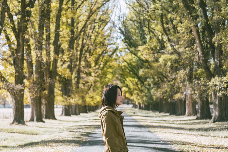 Young woman standing on road against trees in park during sunny day