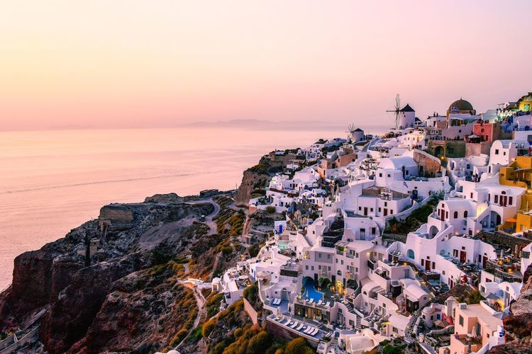 Houses By Sea Against Sky During Sunset At Santorini