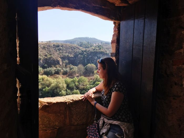 Young woman looking through window against landscape