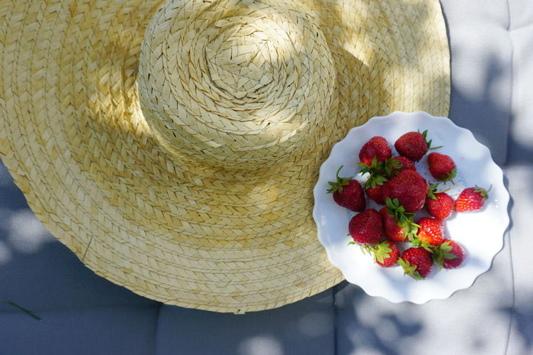 Close-up high angle view of strawberries in plate by hat on table