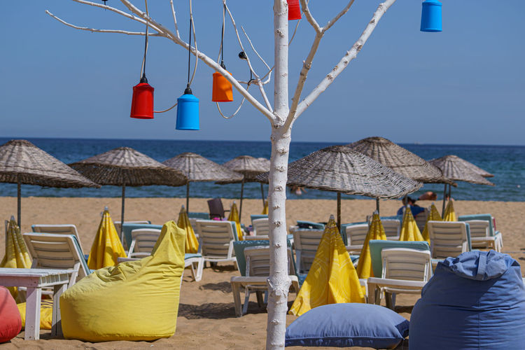 Chairs and parasols on beach against clear sky