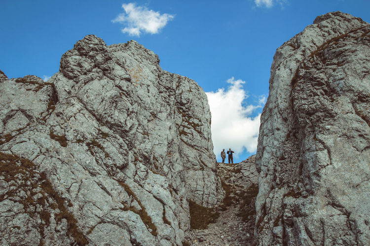 Adventure Beauty In Nature Cliff Cloud - Sky Day Geology Hiking Landscape Leisure Activity Lifestyles Low Angle View Men Mountain Nature Outdoors Physical Geography Real People Rock - Object Rock Formation Rocky Mountains Scenics Sky Standing Vacations Women