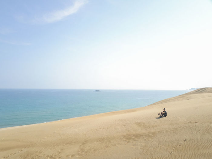 One Person Environment Tranquil Scene Landscape Clear Sky Day Tranquility Nature Copy Space Sand Horizon Over Water Beach Beauty In Nature Scenics - Nature Horizon Sky Water Sea Land Non-urban Scene Idyllic Real People Outdoors Climate