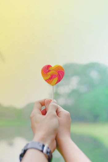 Close-up of couple holding heart shape candy