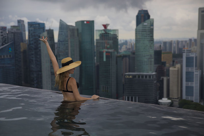 Young girl in a straw hat having fun in the Infinity Pool, Marina Bay Sands, Singapore. ASIA Enjoying The View Hat Holiday Infinity Pool Marina Bay Sands Singapore Aerial Architecture Blonde Girl Building Exterior Landmark Leisure Activity Posing Vacation