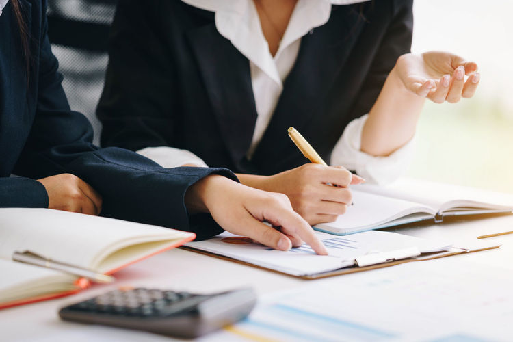 Business woman holding a pen pointing the report and partnership to analyze the marketing plan with calculator on wooden table in office. Brainstorming Business Discussing Discussion Economy Improvement Meeting Planning Teamwork Workplace Accountant Analysis Businesswoman Calculator Consultant Consulting Document Financial Graph Management Project Report Sales Startup Strategy