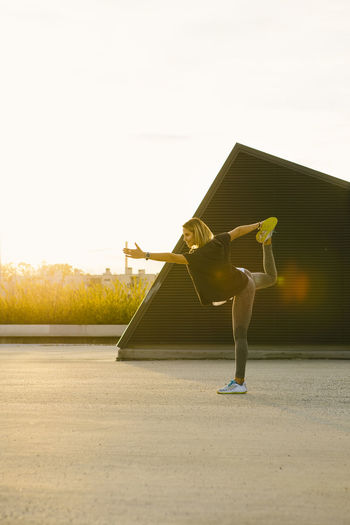 Sporty fit girl doing yoga pose of a swallow during sunset Yoga Yoga Pose Adult Architecture Building Exterior Built Structure Casual Clothing Clear Sky Day Effort Full Length Leisure Activity Lens Flare Lifestyles Nature One Person Outdoors Real People Skill  Sky Sunlight Women Young Adult