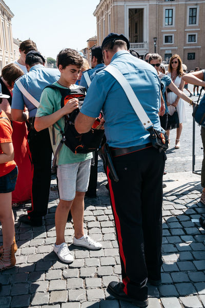 Policeman inspecting the bag of a tourist in Vatican City City DAESH Policeman Rome Security Tourist Travel Vatican Architecture Building Exterior Built Structure Capital Cities  Carabinieri Casual Clothing Destination Full Length Inspecting Inspection Italy Landmark Outdoors Real People Standing Terrorism Tourism