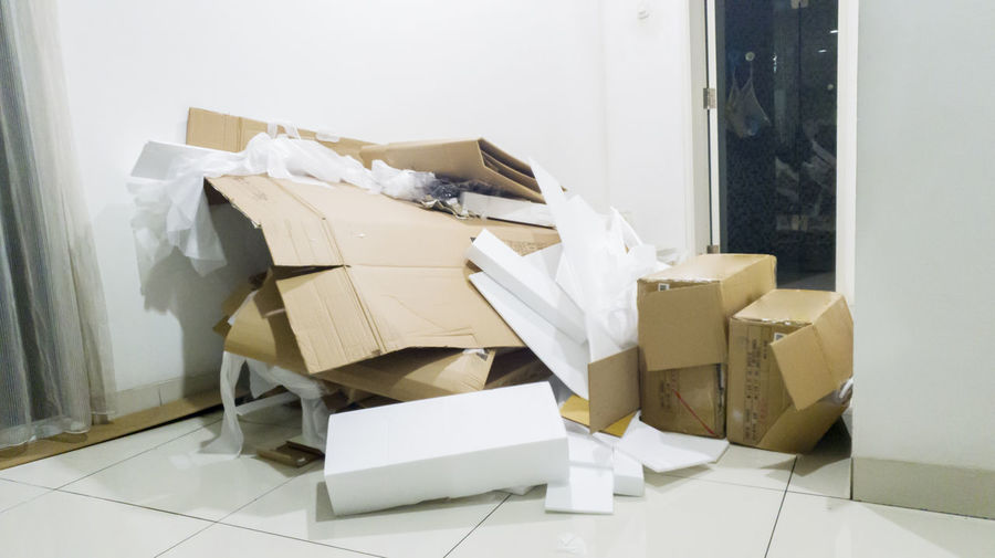 Broken cardboard boxes and polystyrene on tiled floor at home