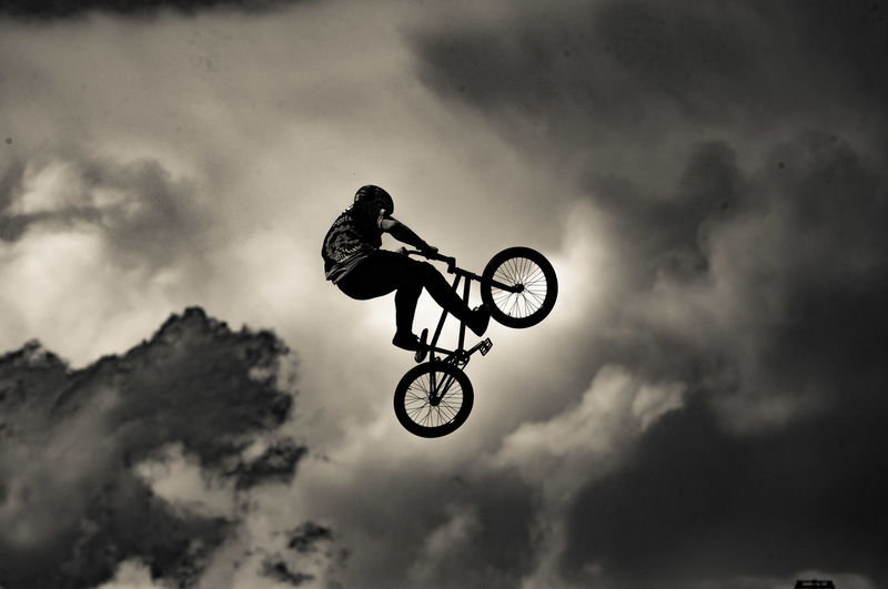 Man performing bicycle stunt against sky