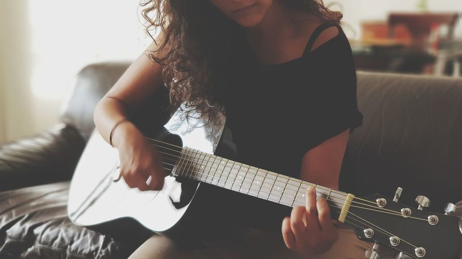Midsection of woman playing guitar on sofa at home