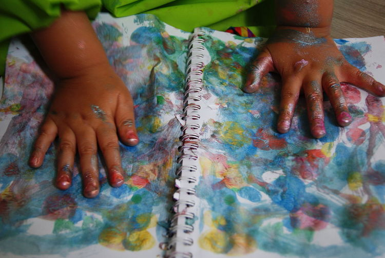 Cropped image of messy child hands over book