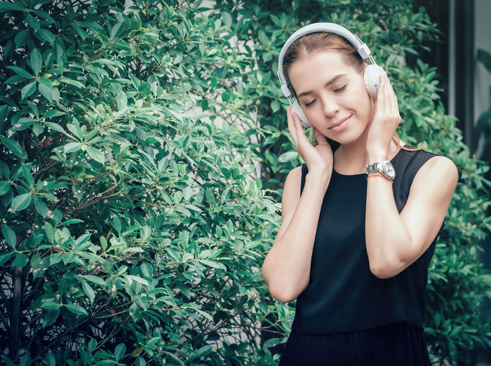 Young Woman Listening Music While Standing Against Plants