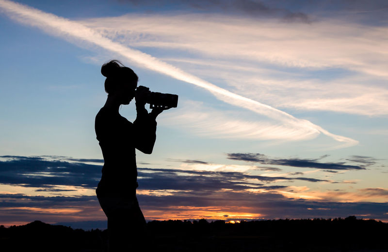 Silhouette woman photographing against sky during sunset
