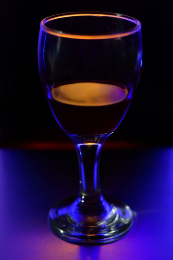 Close-up of beer glass on table against black background