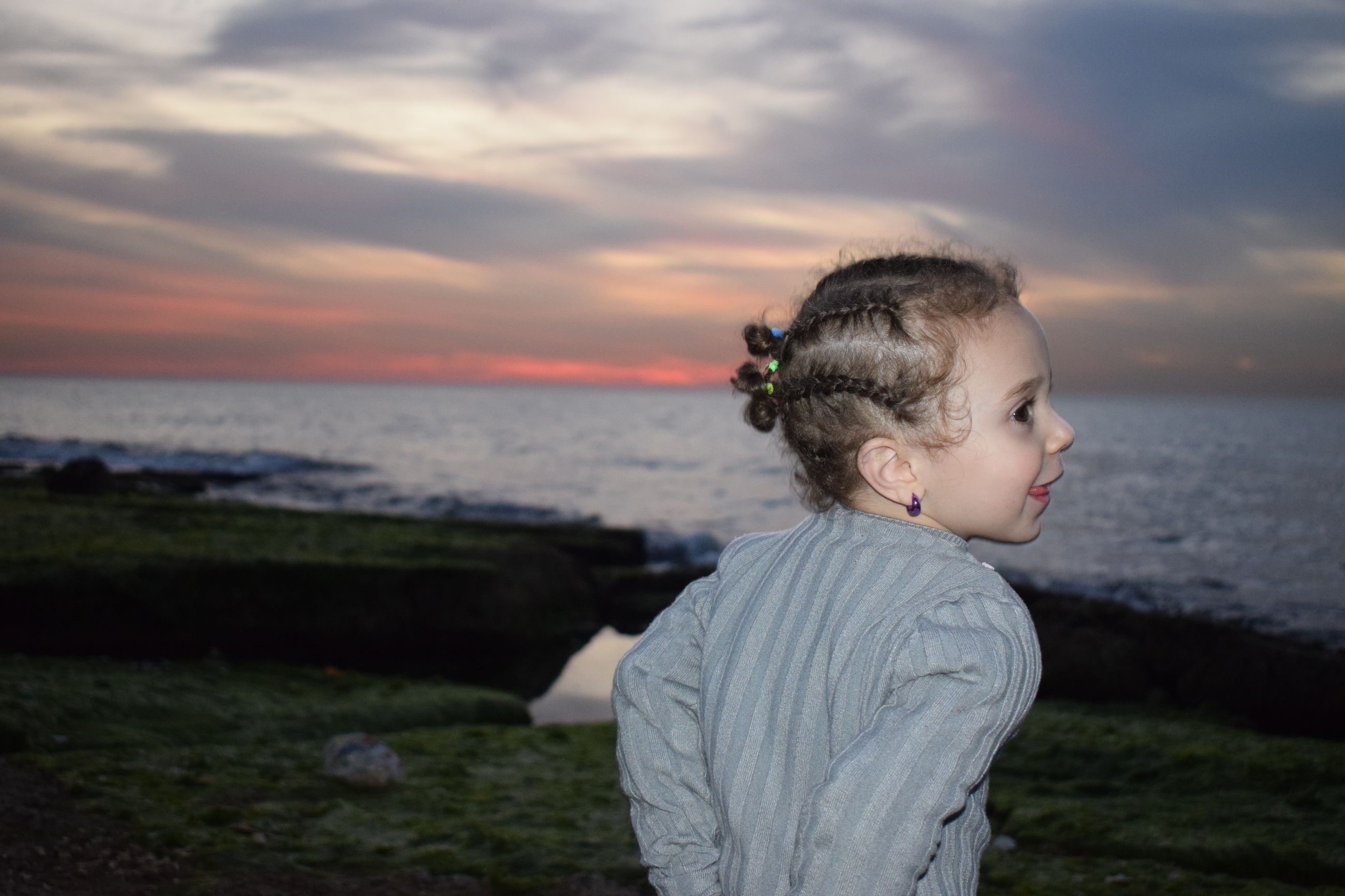 water, sea, sky, childhood, child, leisure activity, one person, lifestyles, land, real people, cloud - sky, standing, sunset, nature, beauty in nature, beach, boys, casual clothing, horizon over water, innocence, outdoors, contemplation
