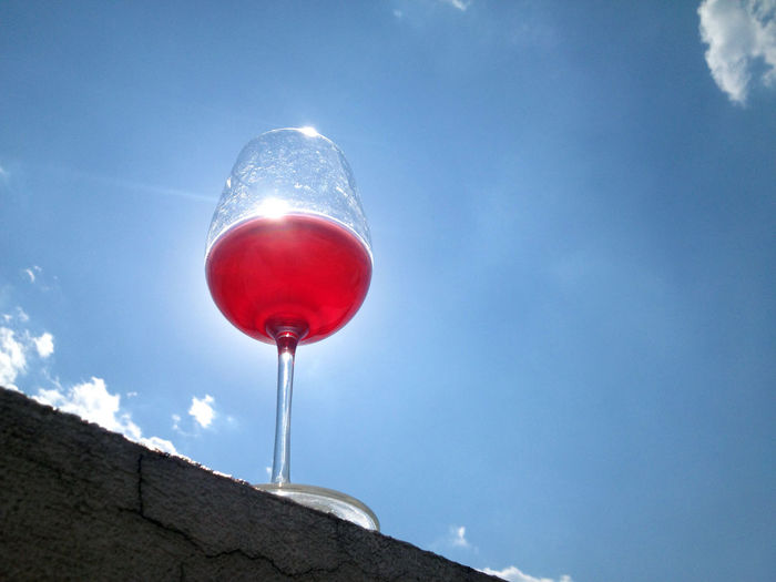 Low angle view of wine glass against blue sky