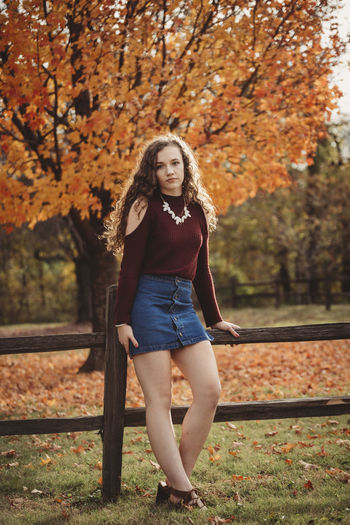 Portrait of beautiful young woman with autumn tree