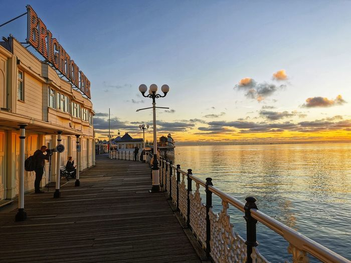 Street leading towards pier against sky during sunset