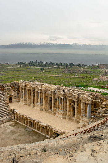 The earthquake damaged roman ruins of an auditorium and other buildings at the top of Pamukkale, Turkey with snow capped mountains in the background. Turkey Ancient Ancient Civilization Ancient History Arch Archaeology Architectural Column Architecture Built Structure Cloud - Sky Day History Nature No People Old Old Ruin Outdoors Pamukkale Ruined Sky The Past Tourism Travel Travel Destinations