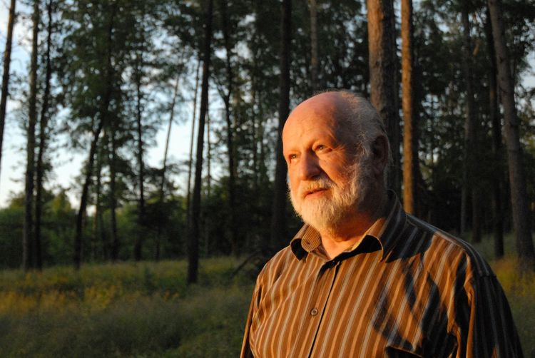 Thoughtful senior man standing in forest during sunset