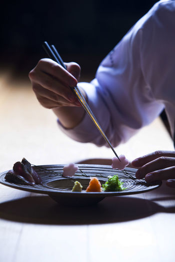Midsection of man eating food in plate on table