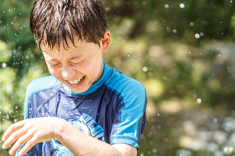 Water Spraying Over Cheerful Boy At Yard