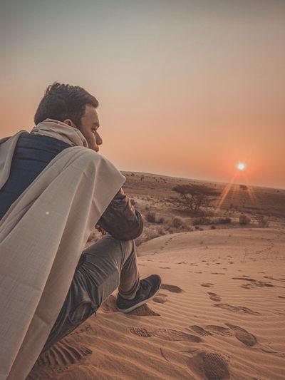 Rear view of man sitting on desert against sky during sunset