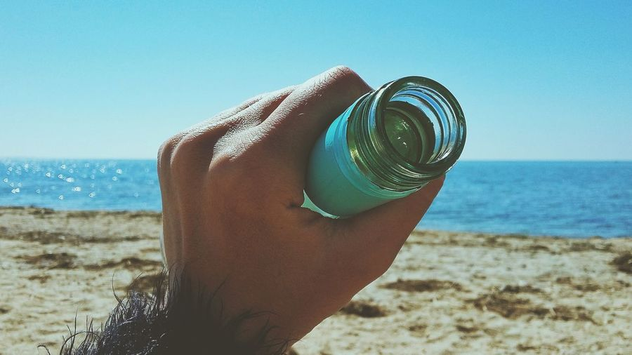 Close-up of hand holding blue sea against clear sky