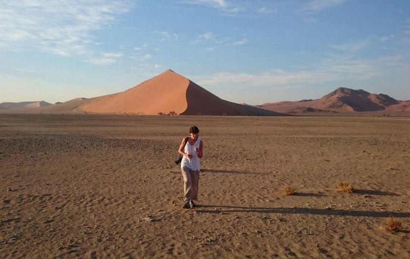 Mature woman walking on desert against sky