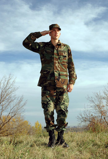A young military solider stands at attention on a hilltop against a cloudy blue sky