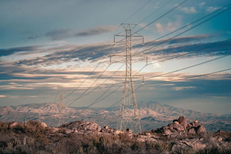 Electricity pylon running downhill against sky with four peaks in scottsdale arizona