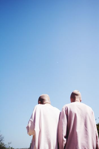 Low Angle View Of Men With Shaved Head Against Blue Sky