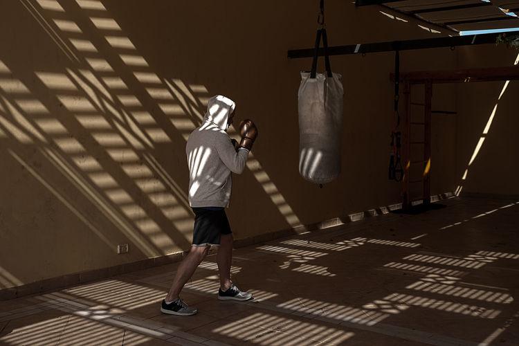 Man wearing hoodie standing by punching bag
