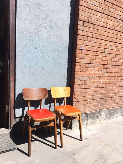 Two peas in a pod. London Shoreditch, London Chair Seat Empty Sunlight Absence Wall - Building Feature Built Structure Architecture Furniture Outdoors Wood - Material Shadow Orange Color Building Exterior Building No People Day Wall Table