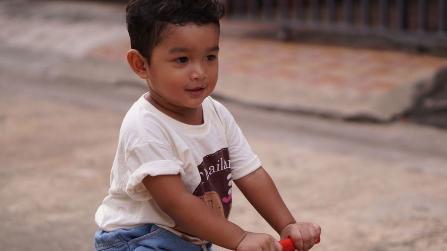 Cute baby boy playing with toy on land