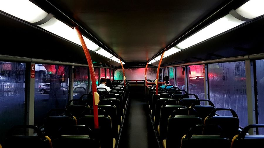 Rear view of man and woman sitting in bus at night