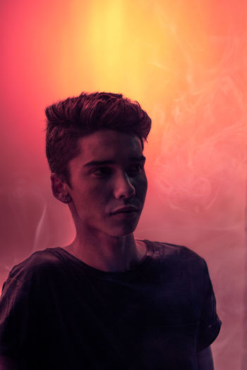 Portrait of teenage boy looking away against colored background