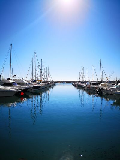 Sailboats moored in marina against blue sky