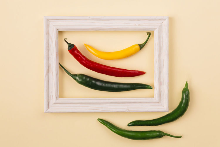 Directly above shot of yellow chili peppers on white background