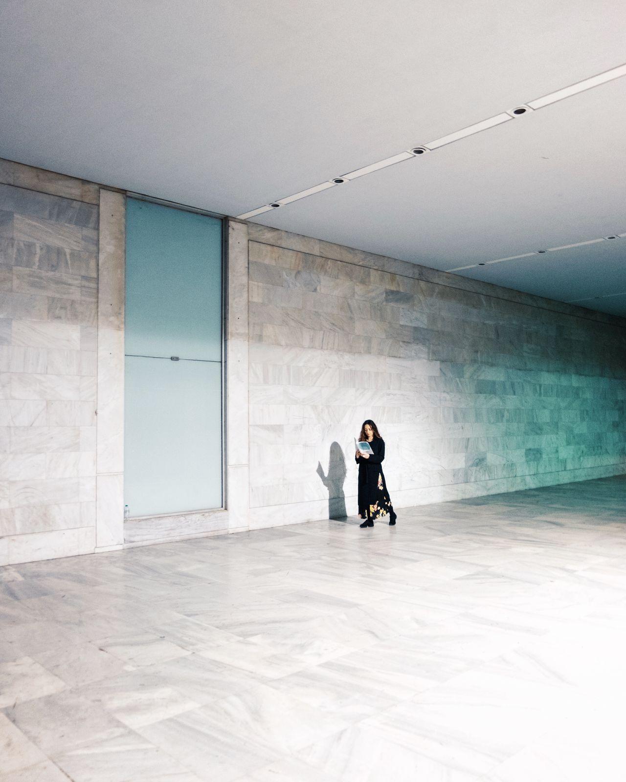 Woman reading book while walking in corridor