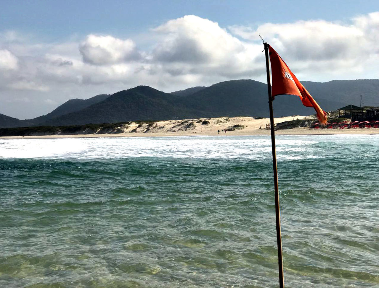 mountain, water, flag, sky, sea, cloud - sky, beauty in nature, motion, nature, scenics - nature, patriotism, no people, day, mountain range, waterfront, tranquil scene, beach, land, outdoors, wind