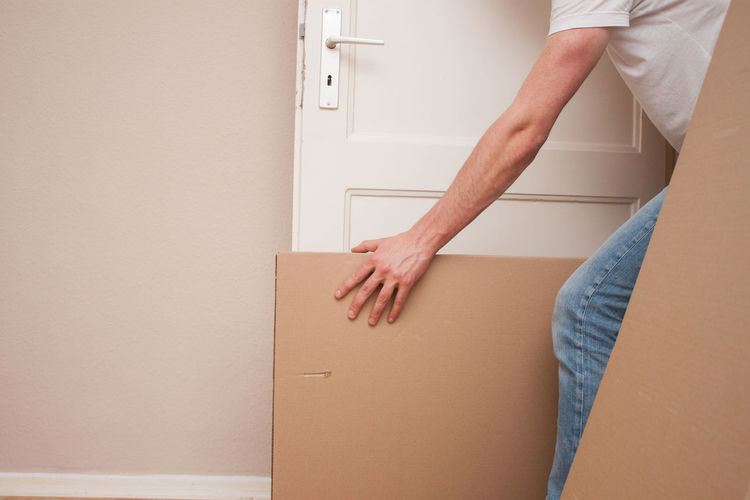 Midsection Of Man Carrying Cardboard Box At Home